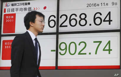 A man walks by an electronic stock board of a securities firm in Tokyo, Nov. 9, 2016.