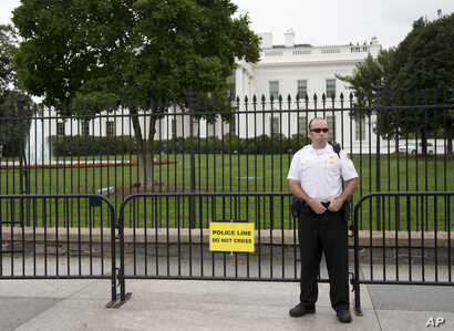 FILE - A member of the United States Secret Service Uniformed Division looks out over Pennsylvania Avenue as he stands in front of a temporary barrier in front of the White House in Washington, Oct. 3, 2014.