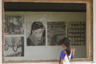 FILE - A Cambodian girl looks at images of Khmer Rouge victims displaying at Tuol Sleng genocide museum, formerly the regime's notorious S-21 prison in Phnom Penh, Cambodia, March 26, 2015.