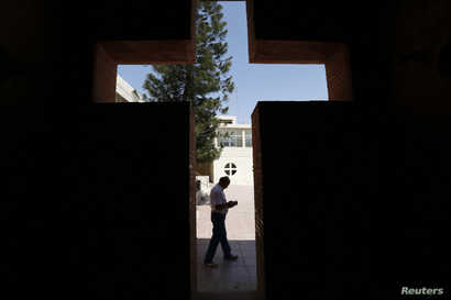 An Iraqi Christian man from Mosul, who fled with his family from violence in their country, reads a book at the Latin Patriarchate Church in Amman, Jordan, Aug. 21, 2014.