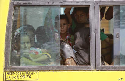 Indians living close to the border with Pakistan board a bus to move to safer places after authorities ordered the evacuation of villages near the highly militarized Line of Control dividing Kashmir between India and Pakistan, at Narana village in Pa...