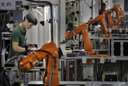 FILE - In this Aug. 21, 2015 photo, a Chinese man works amid orange robot arms at Rapoo Technology factory in southern Chinese industrial boomtown of Shenzhen.