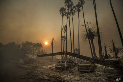 Smoke rises behind a leveled apartment complex as a wildfire burns in Ventura, Calif., on Tuesday, Dec. 5, 2017.