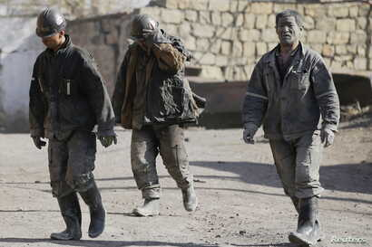 FILE - Miners are seen walking at one of the coal mines of the state-owned Longmay Group on the outskirts of Jixi, in Heilongjiang province, China, Oct. 24, 2015.