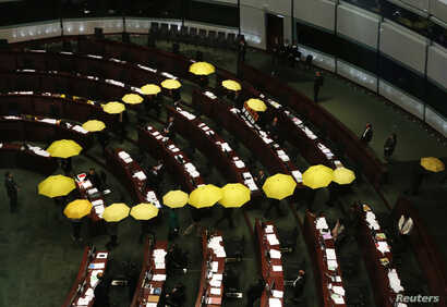 Pro-democracy lawmakers carrying yellow umbrellas, symbols for the Occupy Central movement, leave in the middle of a Legislative Council meeting as a gesture to boycott the government in Hong Kong January 7, 2015. Hong Kong's government is set to lau...