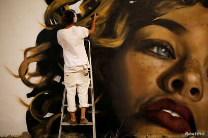 American artist, who goes by the name Drew works on his wall painting during an art happening, called POW! WOW! Israel, which is connected to a week-long art and culture festival held in Hawaii called POW! WOW! Hawaii, in the southern city of Arad, I...