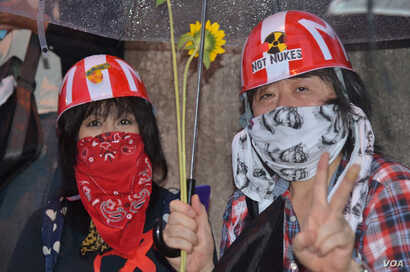 Rain-soaked protesters, Tokyo, Japan, July 6, 2012. (S.L. Herman/VOA)