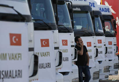 A driver waits in front of trucks carrying humanitarian aid destined for Idlib, Syria, by a Turkish pro-government aid group, prior to their departure in Istanbul, Sept. 10, 2018.
