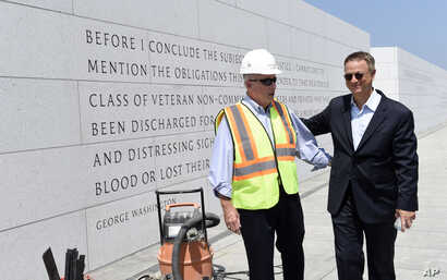 FILE - Actor Gary Sinise, right, talks with Arthur H. Wilson,  co-founder of the Disabled Veterans' Life Memorial Foundation, Inc., left, as they tour the new American Veterans Disabled For Life Memorial in Washington, Aug. 20, 2014.