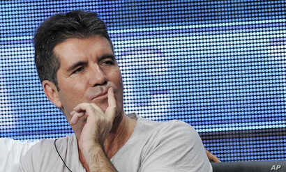 "Simon Cowell, a judge on the FOX series ""The X Factor,"" looks on from the stage during a panel discussion on the show at the FOX 2013 Summer TCA press tour at the Beverly Hilton Hotel, Aug. 1, 2013."