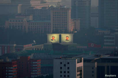 FILE - Portraits of late North Korean leaders Kim Il Sung and Kim Jong Il are seen early morning at a memorial park in Pyongyang, North Korea, Sept. 8, 2018.