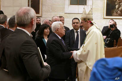 Palestinian President Mahmoud Abbas congratulates Archbishop Pierbattista Pizzaballa, apostolic administrator of the Latin Patriarch of Jerusalem, during the Christmas Midnight Mass in Saint Catherine's Church at the Church of the Nativity, in Bethle...