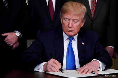 FILE - U.S. President Donald Trump signs a memorandum on intellectual property tariffs on high-tech goods from China, at the White House in Washington, DC, U.S., March 22, 2018.