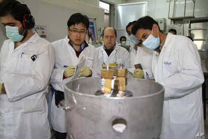 FILE - Unidentified International Atomic Energy Agency inspectors and Iranian technicians cut the connections between the twin cascades for 20 percent uranium enrichment at Natanz facility, 322 kilometers from Tehran, Iran, Jan. 20, 2014.