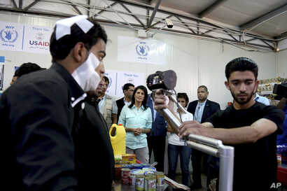 U.S. Ambassador to the United Nations Nikki Haley, background center, looks on as a bandaged Syrian refugee has his iris scanned at a supermarket, May 21, 2017, in Zaatari Refugee Camp, Jordan.