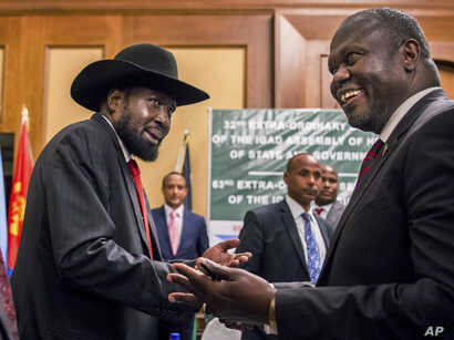 FILE - In this file photo dated June 21, 2018, South Sudan's President Salva Kiir, left, and opposition leader Riek Machar, right, shake hands during peace talks in Addis Ababa, Ethiopia. r