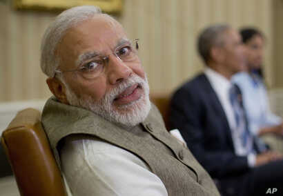 Indian Prime Minister India Narendra Modi looks over his shoulder to speak with an aide during his meeting with President Barack Obama in the Oval Office of the White House in Washington, June 7, 2016.