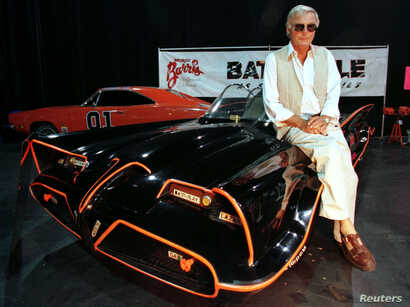 "FILE - Actor Adam West, who portrayed the title character in the 1960's television series ""Batman,"" poses atop the original Batmobile used in the hit series."