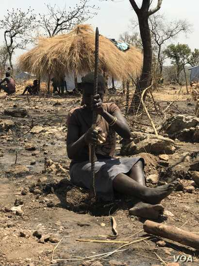 Susan, 23, digs to build a thatched house in the Imvempi refugee settlement in Arua district, Uganda, Jan. 30, 2018. (H. Athumani/VOA)
