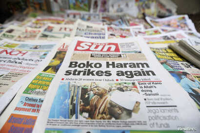 FILE - A newspaper with its front page headline on an abduction of women from a village in northeast Nigeria is displayed at a vendor's stand along a road in Ikoyi district in Lagos, Nigeria, June 10, 2014.