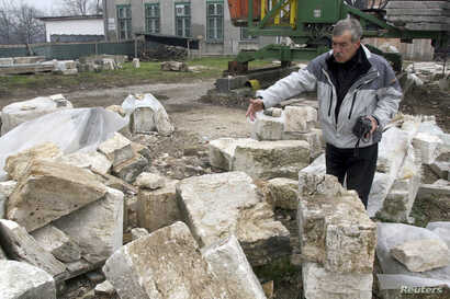FILE - A Bosnian construction worker shows remains of the blown up Ferhadija mosque in Banja Luka, Dec. 10, 2008.