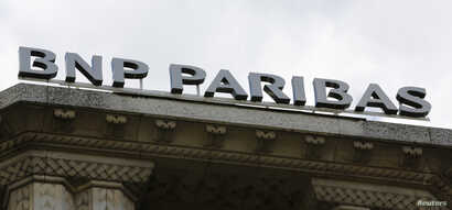 The logo of  French bank BNP Paribas is seen above the facade of their central Paris agency June 30, 2014.