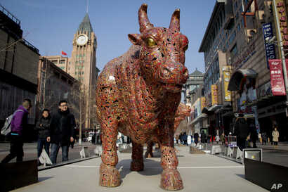 """People walk by bull sculptures titled """"Five Bulls Gathering Fortune"""" on display at the Wangfujing shopping district in Beijing, Jan. 10, 2019. Uncertainty over the outcome of China-U.S. trade talks is casting a pall over Asian markets as both sides k..."""