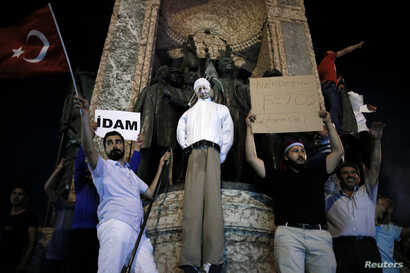 Supporters of Turkish President Tayyip Erdogan hold an effigy of U.S.-based cleric Fethullah Gulen hanged by a noose on the Republic Monument, during a pro-government demonstration on Taksim Square in Istanbul, Turkey, July 18, 2016. The placards rea...