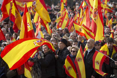 People wave Spanish flags during a rally by the right wing VOX party in Madrid, Dec. 1, 2018. VOX supporters waved Spanish flags as they gathered in Colon Square to listen to speeches from party leaders.