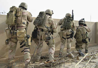 \A team of U.S. Navy SEALs fires on insurgents from a rooftop in this April 2006 file photo in Ramadi, Iraq. (AP)