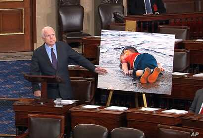Republican Sen. John McCain displayes a photo of the body of a three year-old Syrian refugee during a speech urging stronger leadership from President Barack Obama on Syria, Sept. 9, 2015.