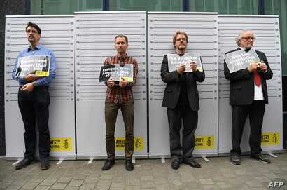 FILE - Former and current heads of Amnesty International in Belgium, (L-R) Vincent Forest, Francois Graas, Rik Vereecken and Willy Laes, stage a mock arrest in front of the Turkish embassy to protest against the detention of Taner Kilic, head of Amne...