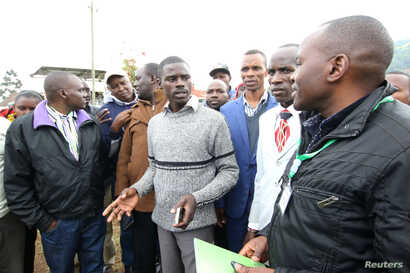 Igembe South parliamentary candidate on an Independent ticket John Paul Mwirigi, center, talks to his agents at their constituency tallying center in Maua Girls High School, in Maua, Kenya, Aug. 9, 2017.