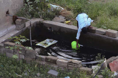 FILE - A man fetches water from a concrete tank in an upcoming residential neighborhood in Bangalore, India, May 3, 2018.