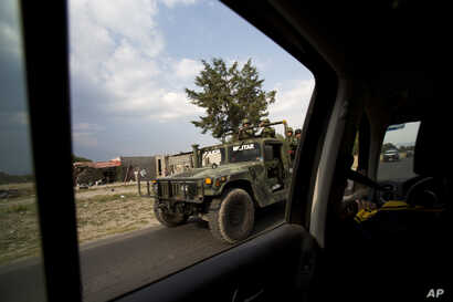 A military convoy patrols a road near Palmarito Tochapan in Puebla State, May 10, 2017. A video released by Mexican media outlets Wednesday appears to show a soldier executing a civilian lying face down in the street in Palmarito Tochapan with a shot...