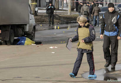 A policewoman walks near the body of a victim covered by a Ukrainian national flag at the site of an attack in Kharkiv, in northeastern Ukraine, Feb. 22, 2015.