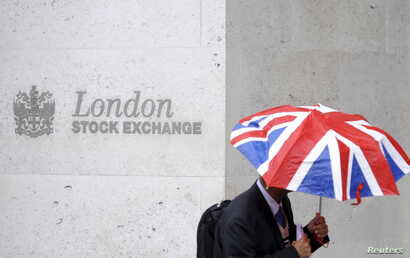 FILE - A worker shelters from the rain as he passes the London Stock Exchange in London.