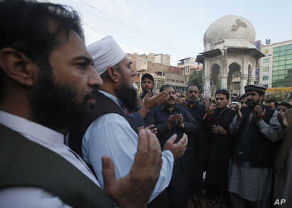 People pray for Pakistani police officer Tahir Dawar in Peshawar, Pakistan, Nov. 15, 2018.