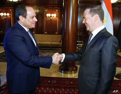 Russian Prime Minister Dmitry Medvedev, right, shakes hands with Egyptian President Abdel-Fattah el-Sissi during their meeting in Moscow, Oct. 16, 2018.