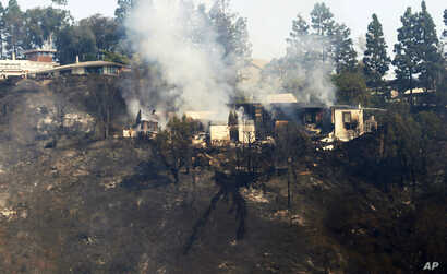 A multimillion-dollar home is a smoldering ruin after a wildfire swept through the Bel Air district of Los Angeles, Dec. 6, 2017.