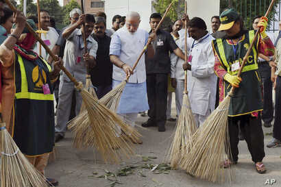 FILE - Indian Prime Minister Narendra Modi, center, sweeps an a road with a broom along with civic workers in New Delhi, Oct. 2, 2014.