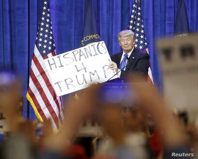 Republican U.S. presidential candidate Donald Trump holds up a sign from the audience as he speaks to supporters at a Super Tuesday campaign rally in Louisville, Kentucky, March 1, 2016.