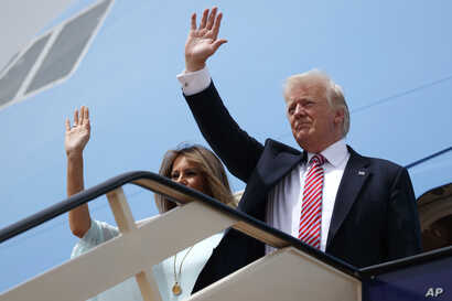 U.S. President Donald Trump, right, and first lady Melania Trump wave as they board Air Force One for Israel, the next stop in Trump's international tour, at King Khalid International Airport, May 22, 2017.