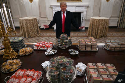 In this Jan. 14, 2019 photo, President Donald Trump talks to the media about the table full of fast food in the State Dining Room of the White House in Washington, for the reception for the Clemson Tigers.