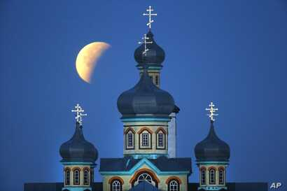 A so-called supermoon is seen at the finish of a lunar eclipse behind an Orthodox church in Turets, Belarus, 110 kilometers (69 miles) west of capital Minsk, Monday, Sept. 28, 2015.