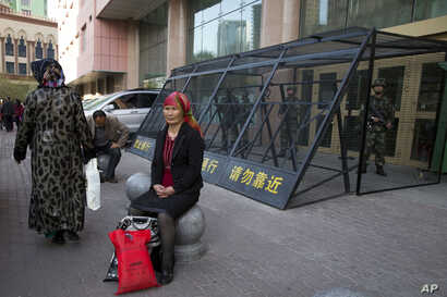 FILE - An Uighur woman rests near a cage protecting heavily armed Chinese paramilitary policemen on duty in Urumqi in China's northwestern region of Xinjiang, May 1, 2014. Uighur homeland has been blanketed with stifling surveillance, from armed chec...