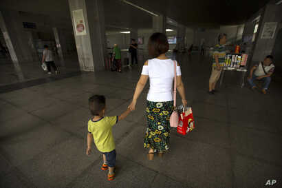 Deng Guilian holds the hand of her son Bo Bo, 3, as they walk through a train station in Ganzhou in southern China's Jiangxi Province, June 7, 2017.