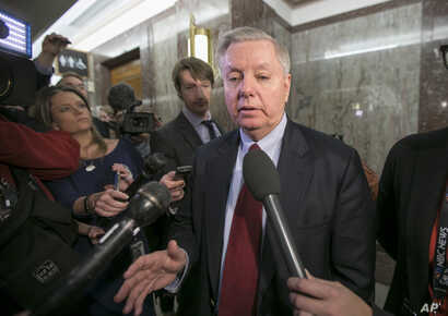Sen. Lindsey Graham, R-S.C., speaks to reporters as he leaves the office of Sen. Susan Collins, R-Maine, who is moderating bipartisan negotiations on immigration, at the Capitol in Washington, Thursday, Jan. 25, 2018.