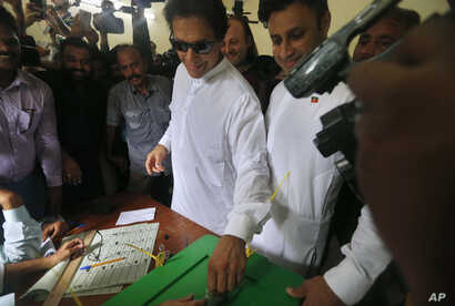 Pakistani politician Imran Khan, center, chief of Pakistan Tehreek-e-Insaf party, casts his vote at a polling station for the parliamentary elections in Islamabad, Pakistan, Wednesday, July 25, 2018.