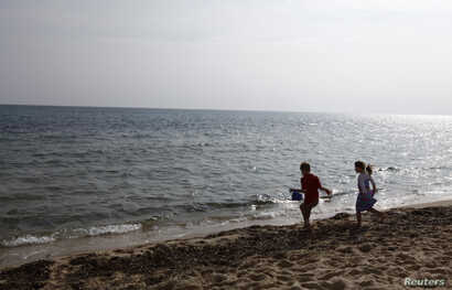 FILE - Children play at a beach in Hammamet, Tunisia, Feb. 19, 2013.